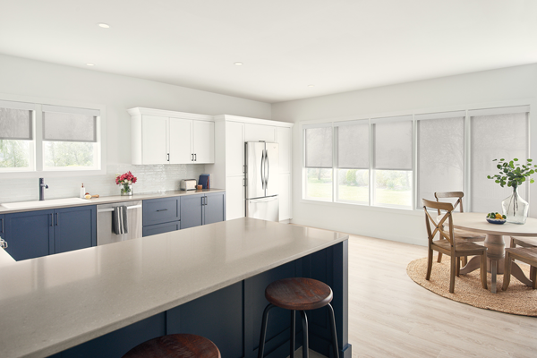 white roller shades in a kitchen with blue and white cabinetry