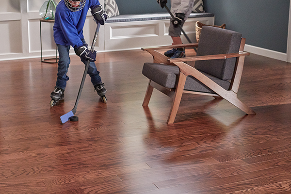boy playing hockey on hardwood flooring in a living room