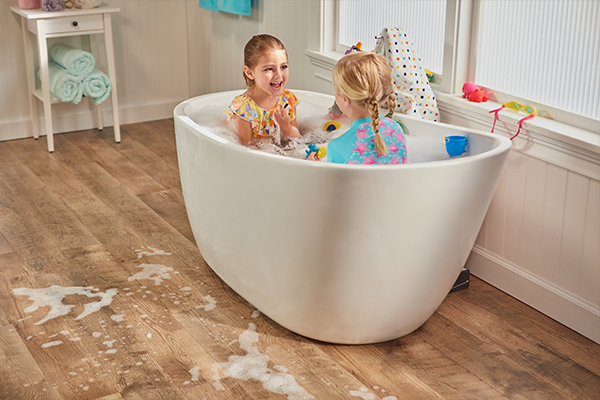 two girls playing in the bathtub in a bathroom with waterproof laminate flooring